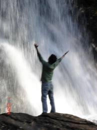 man-under-waterfall